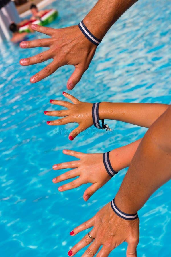 Familjhänder med alla inklusive armband av semesterortsimbassängen fotografering för bildbyråer