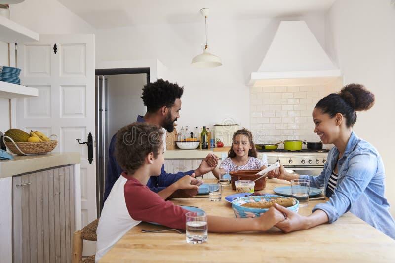 Familjhållhänder runt om köksbordet för deras mål arkivbild
