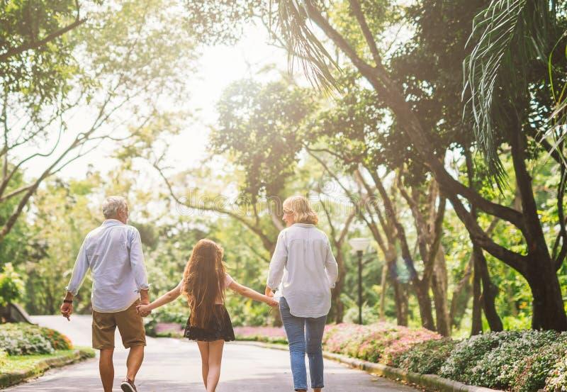 Familjhållhanden och att gå på parkerar fotografering för bildbyråer