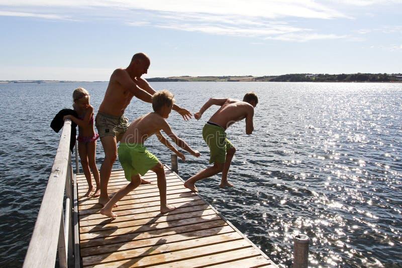 Familjhopp in i havet på sommar i Danmark royaltyfri foto