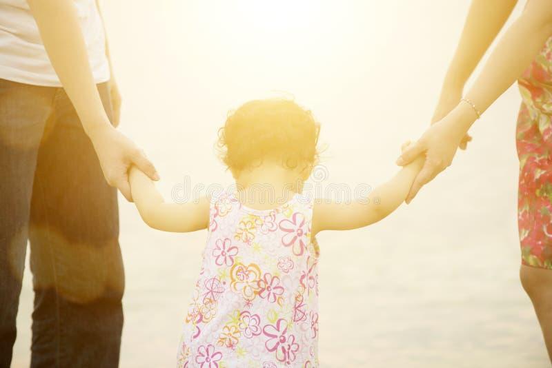 Familjinnehavhänder på sjösidan arkivfoto