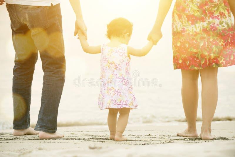 Familjinnehavhänder som går på stranden royaltyfri bild