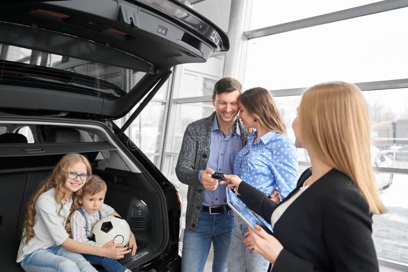 Familjköpandeautomatisk i återförsäljaren, chef som ger biltangenter fotografering för bildbyråer