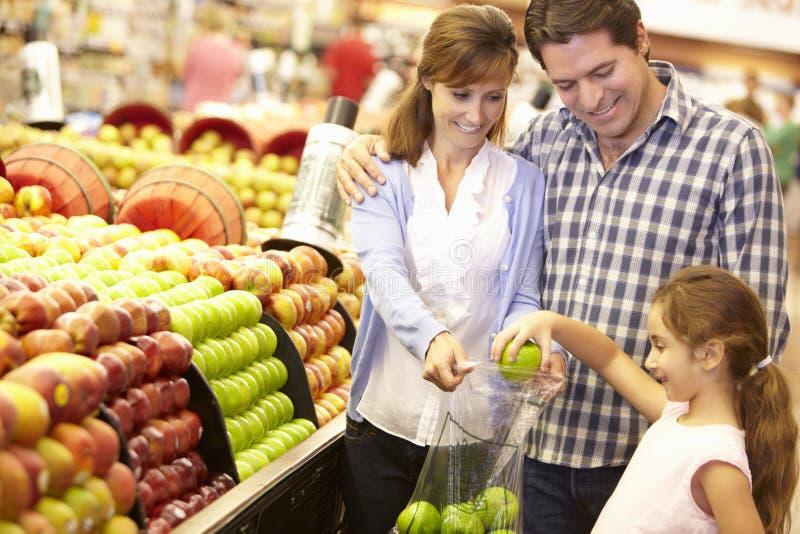 Familjköpandefrukt i supermarket royaltyfria bilder