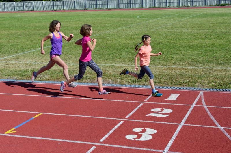 Familjkondition, moder och ungar som kör på stadionspår, utbildning och sund livsstil för barnsport arkivbild