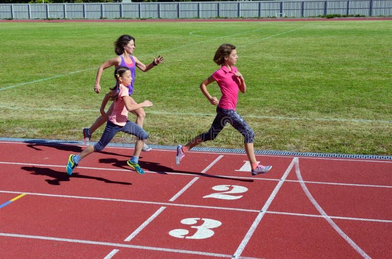 Familjkondition, moder och ungar som kör på stadionspår, utbildning och sund livsstil för barnsport arkivfoto