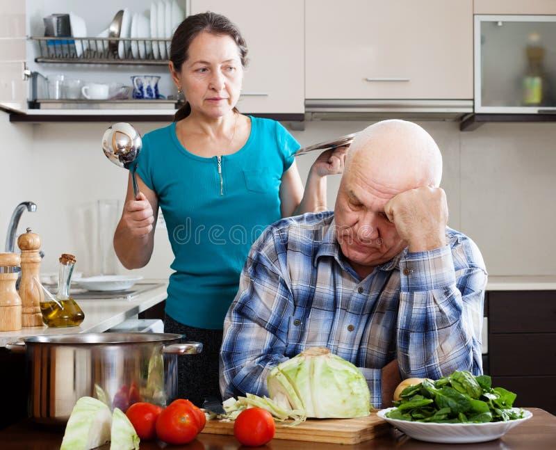 Familjkonflikt.  Den mogna mannen och den ilskna kvinnan under grälar arkivfoto