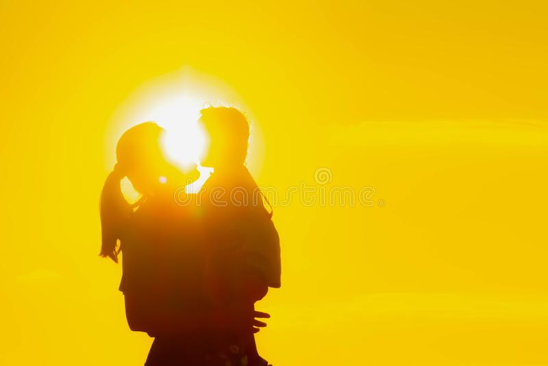 Familjkonturn av st? f?r moder och f?r barn h?ller ?gonen p? solnedg?ngen och himlen i apelsin i afton royaltyfri fotografi