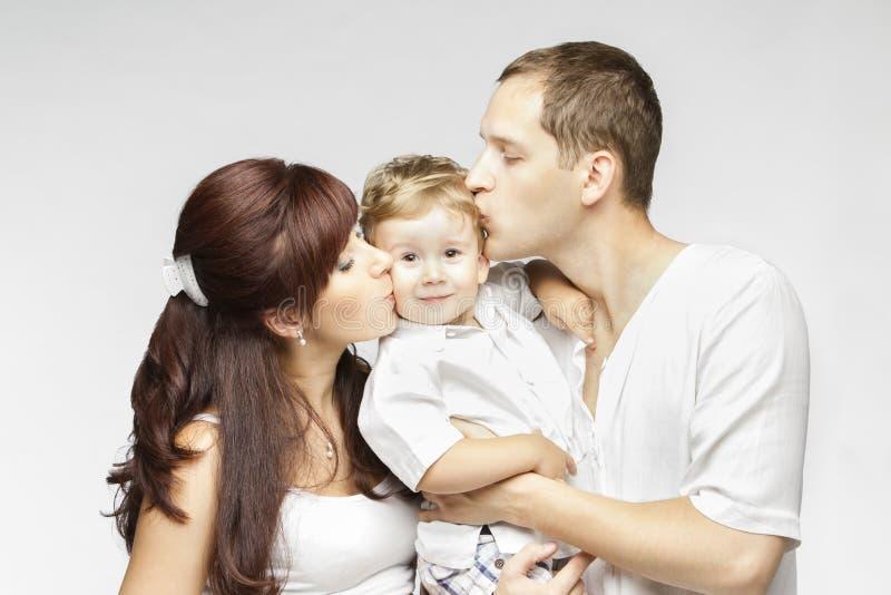 Familjkyss, moderfader Kissing Child, föräldrar och unge arkivfoto