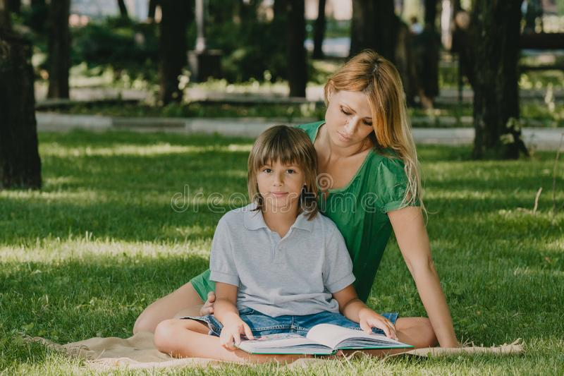 Familjl?sning Mamman och sonen är läseboken på gräs royaltyfri bild