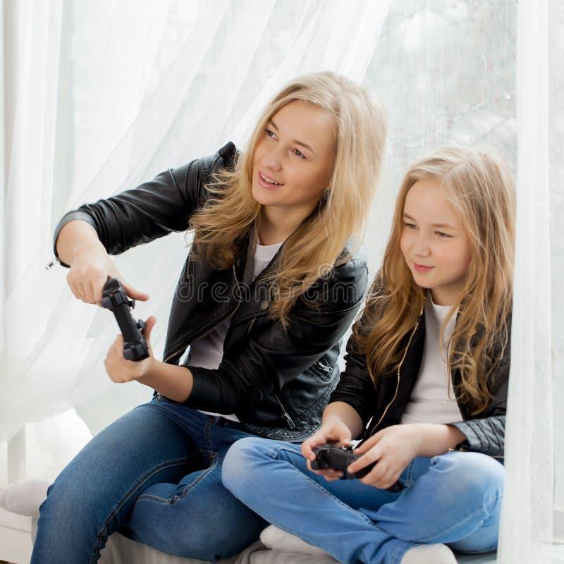 Familjlekar Moder- och dotterlek på conlsole tillsammans sinnesrörelser royaltyfria foton