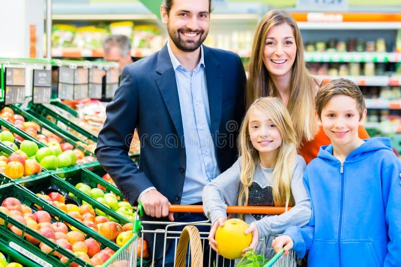 Familjlivsmedelsbutikshopping i stormarknad royaltyfria bilder