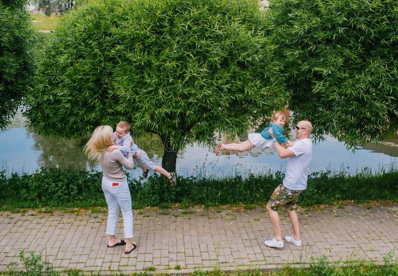 Familjlivsstilståenden av en mum och farsan med deras barn som har bra tid i sommaren, parkerar arkivbilder