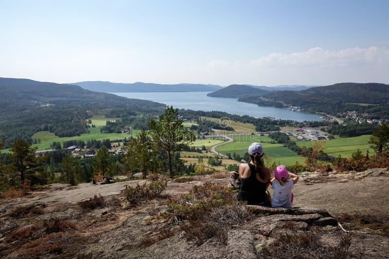 Familjlopp Modern och dottern vilar från att fotvandra berget arkivbilder
