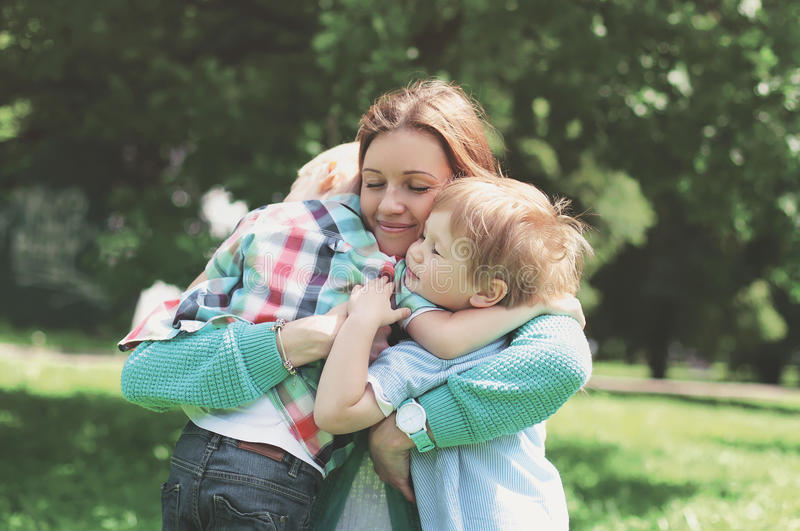 Familjlycka! Lycklig moder som omfamnar ömt hans två söner royaltyfri bild