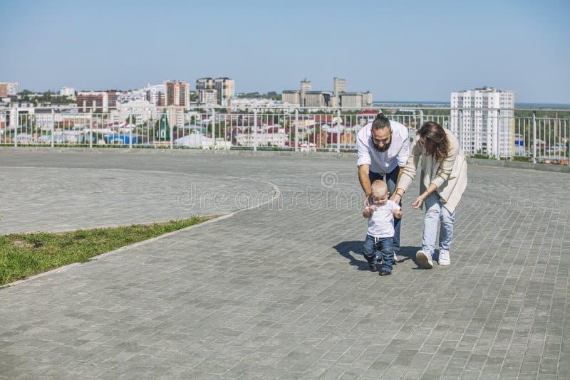 Familjmammafarsan och behandla som ett barn lyckligt med leenden tillsammans i parkeranollan arkivfoto