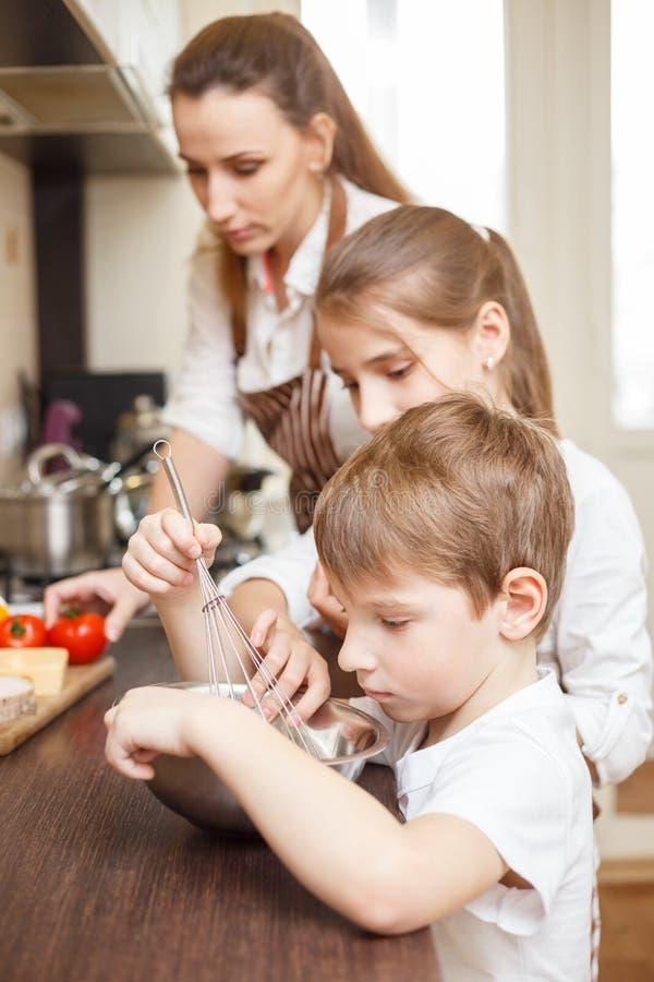 Familjmatlagning Mum och barn i köket royaltyfri foto