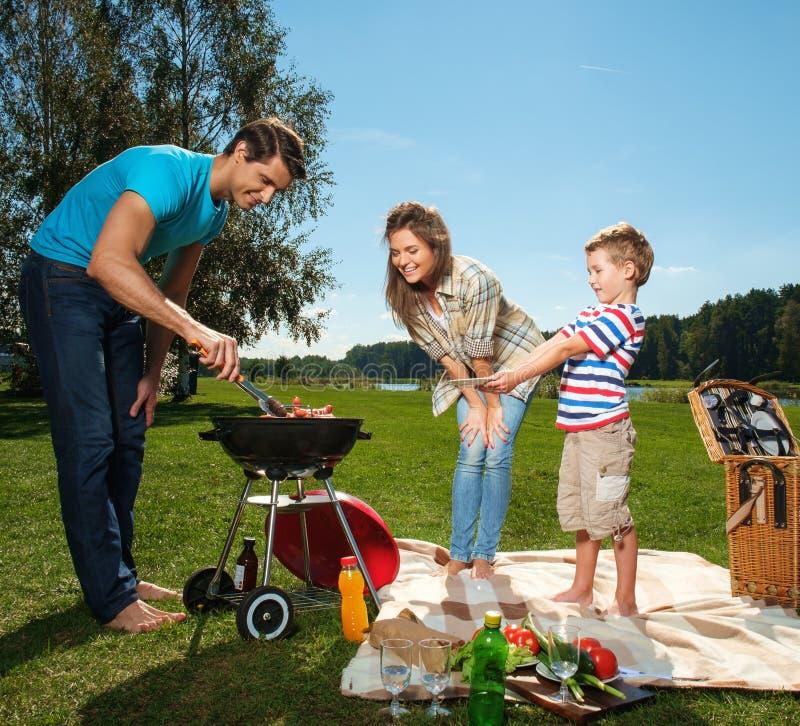 Familjmatlagning på ett galler utomhus fotografering för bildbyråer