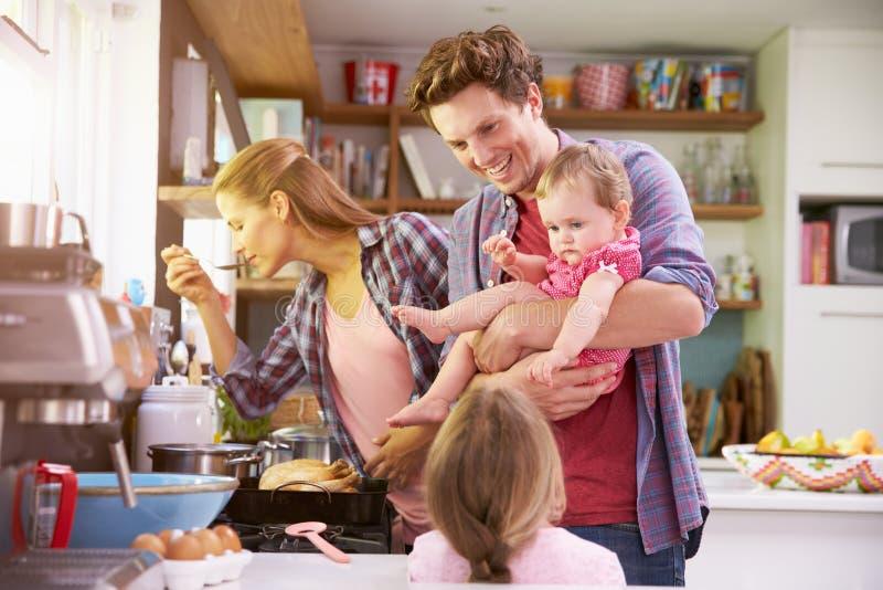 Familjmatlagningmål i kök tillsammans royaltyfria bilder