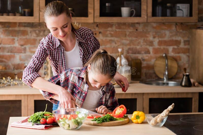 Familjmatlagningmodern undervisar dottern att klippa grönsaken royaltyfria bilder