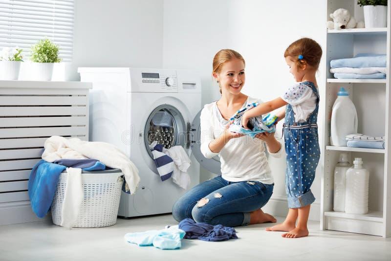 Familjmoder och barnflicka i tvättstuga nära tvagningmachi arkivfoton