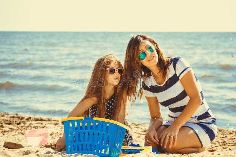 Familjmoder och dotter som har gyckel på stranden arkivbild