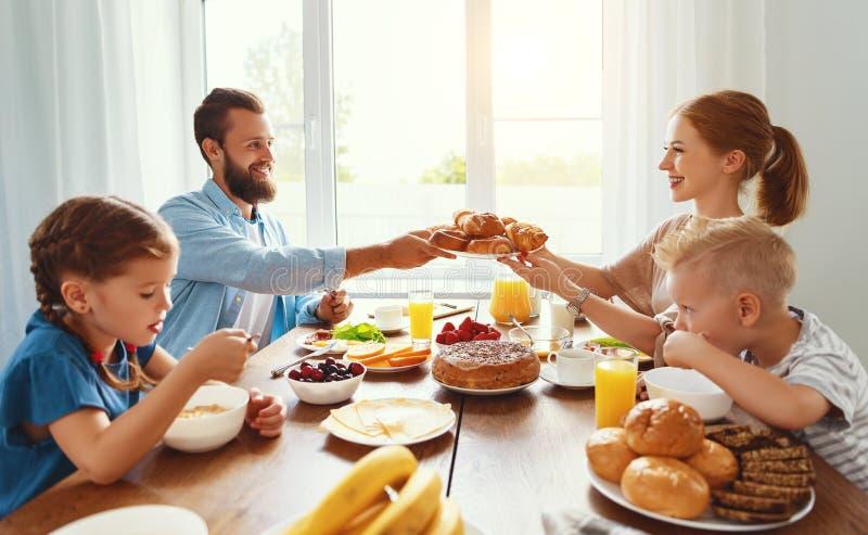 Familjmoderfadern och barn har frukosten i kök i morgon royaltyfria bilder