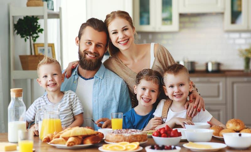 Familjmoderfadern och barn har frukosten i kök i morgon royaltyfri foto