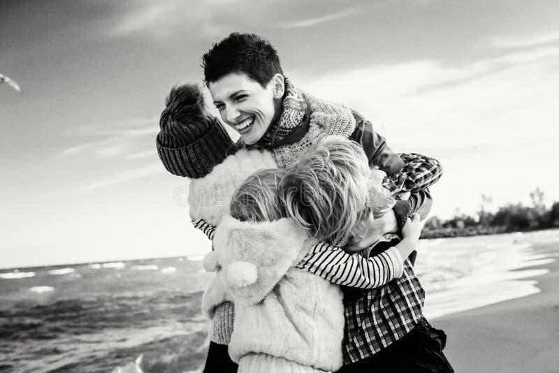 familjmodern med tre barn lurar att krama le att skratta på havhavsstranden arkivbild