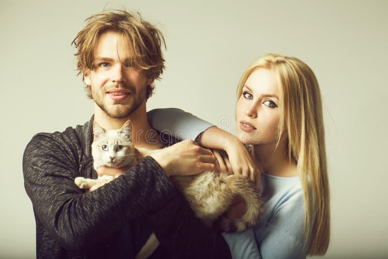 Familjpar som ?r f?r?lskade med katten, kvinnan och den lyckliga mannen royaltyfri fotografi