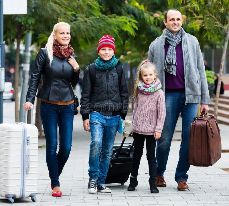 Familjresa: maker med barnatt gå och bagage arkivfoton