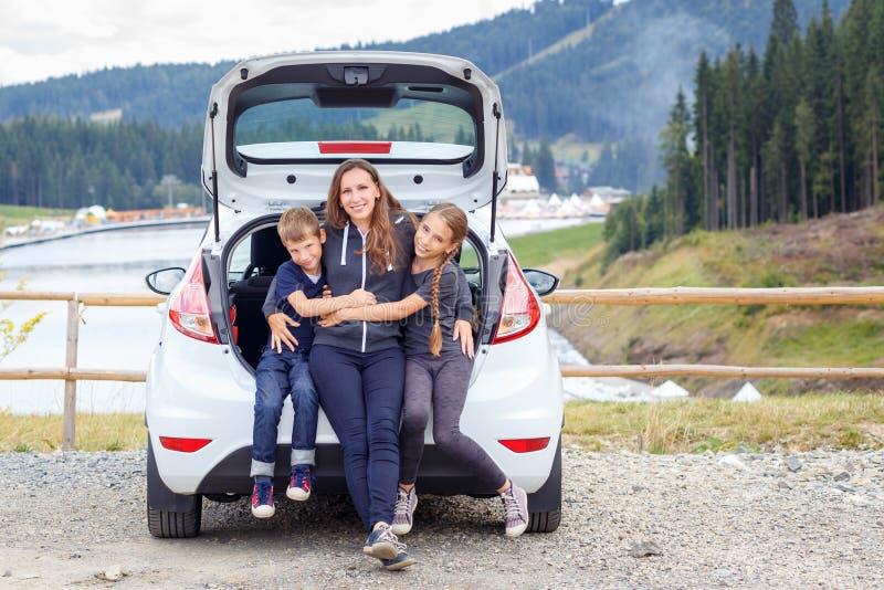 Familjresande med bilen och hagyckel på parkering royaltyfria bilder