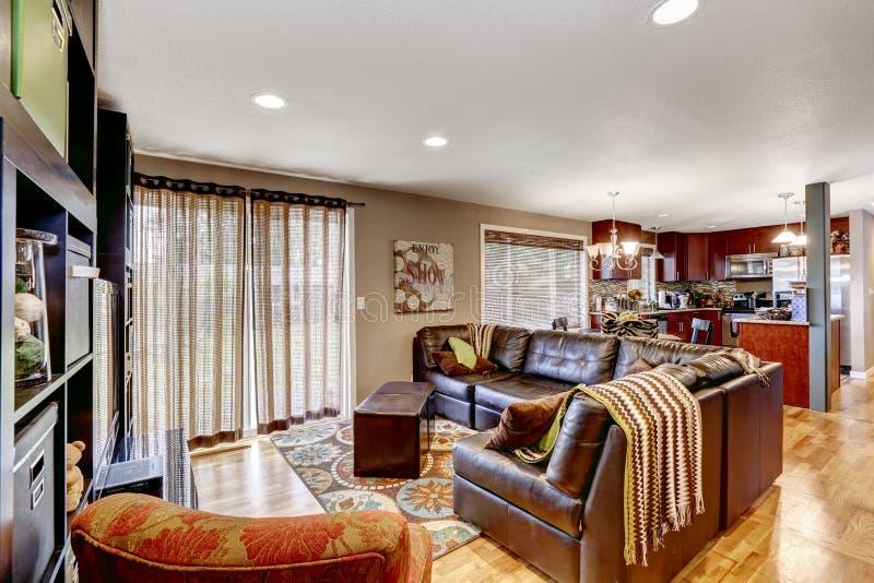 Familjrum med lädersoffa- och kökområde royaltyfri fotografi