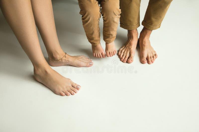 Familjs ben på den vita studiobakgrund, mamman, farsan och sonen royaltyfri bild