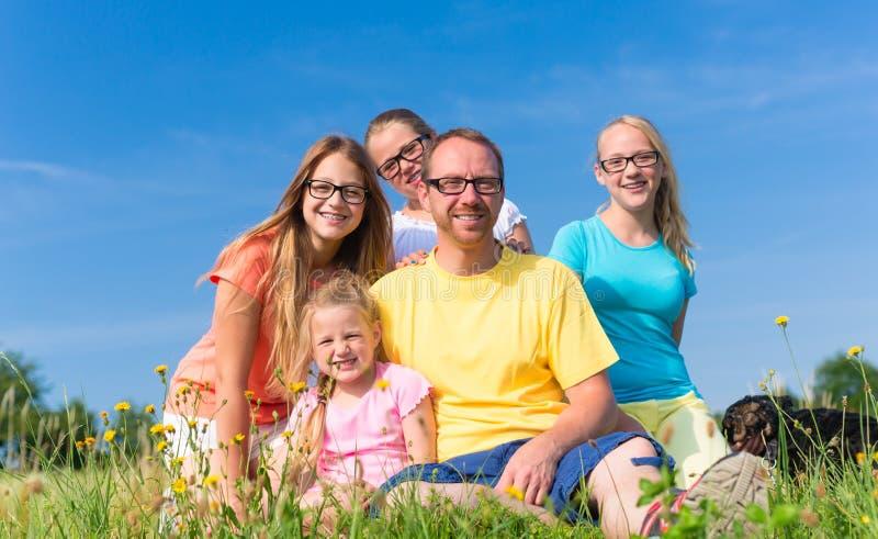 Familjsammanträde på ängen - farsa med barn royaltyfria bilder