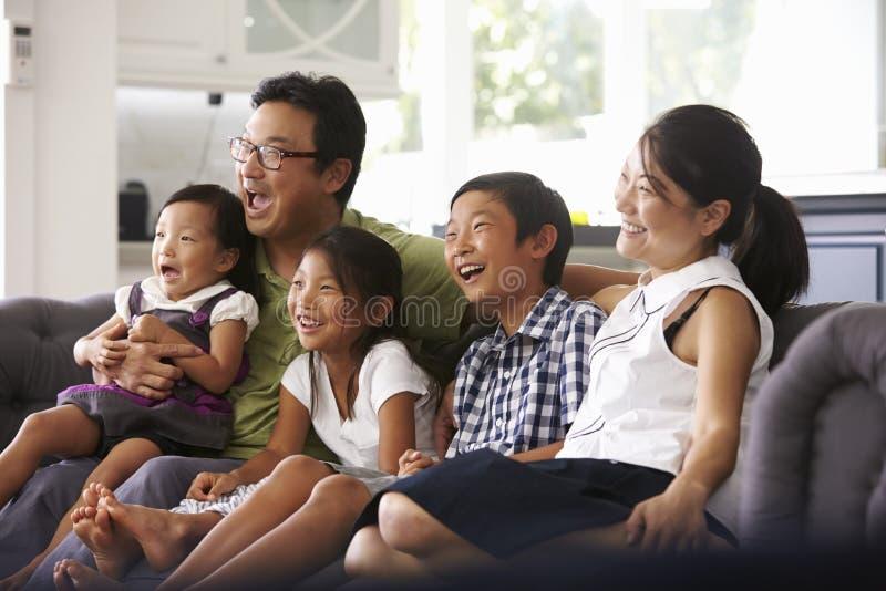Familjsammanträde på Sofa At Home Watching TV tillsammans royaltyfri foto