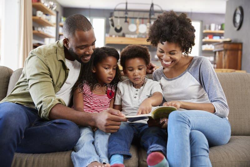 Familjsammanträde på Sofa In Lounge Reading Book tillsammans royaltyfri fotografi