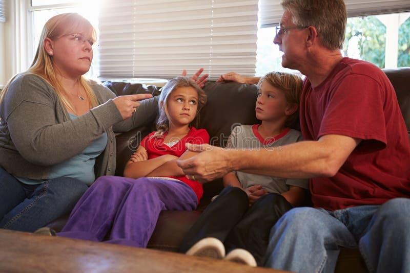 Familjsammanträde på Sofa With Parents Arguing royaltyfri foto