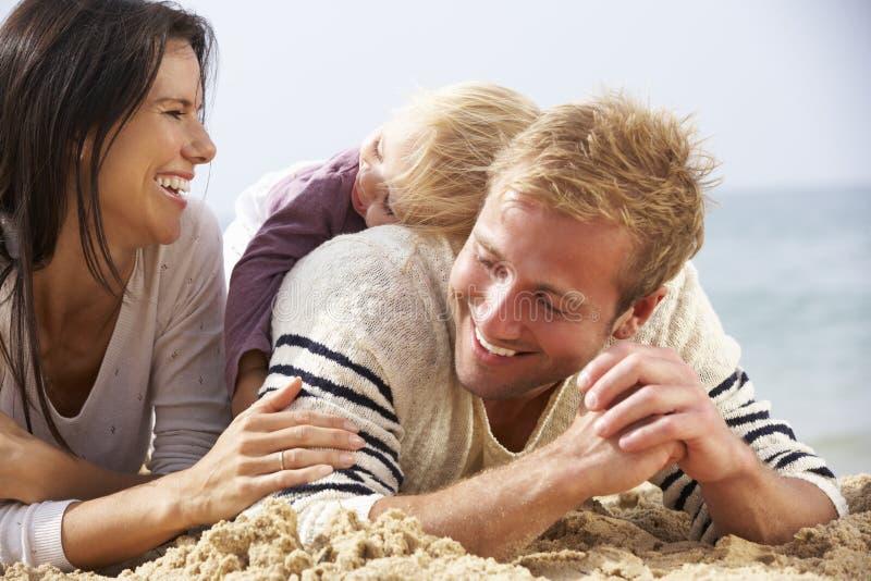 Familjsammanträde på stranden tillsammans arkivfoto