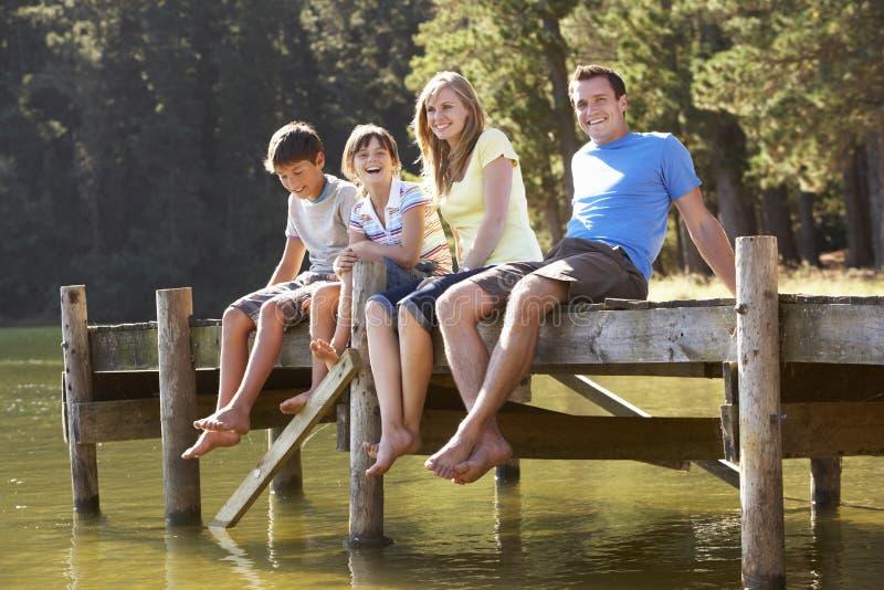 Familjsammanträde på träbryggan som ut ser över sjön arkivbilder