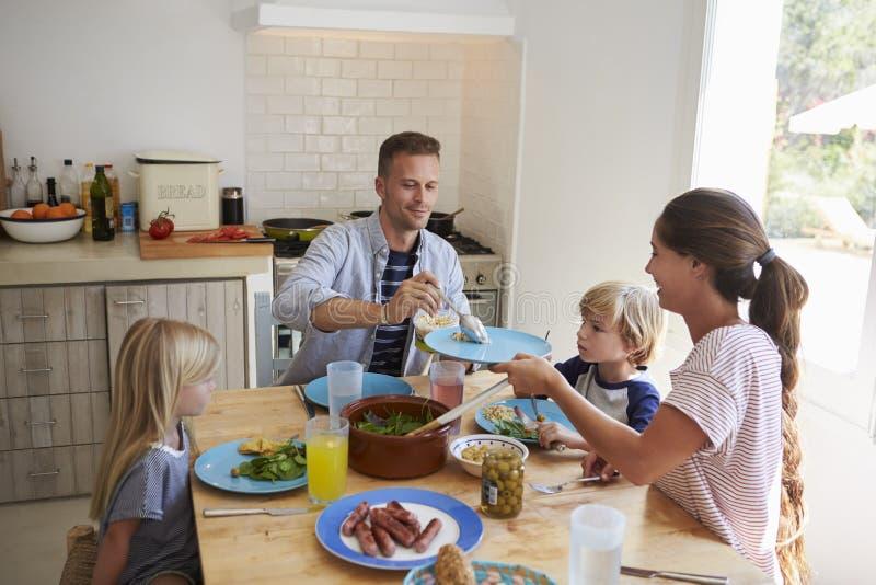 Familjsammanträde runt om köksbordportionlunch arkivfoto