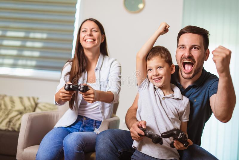 Familjsammantr?de p? soffan som spelar tillsammans videospel royaltyfria bilder