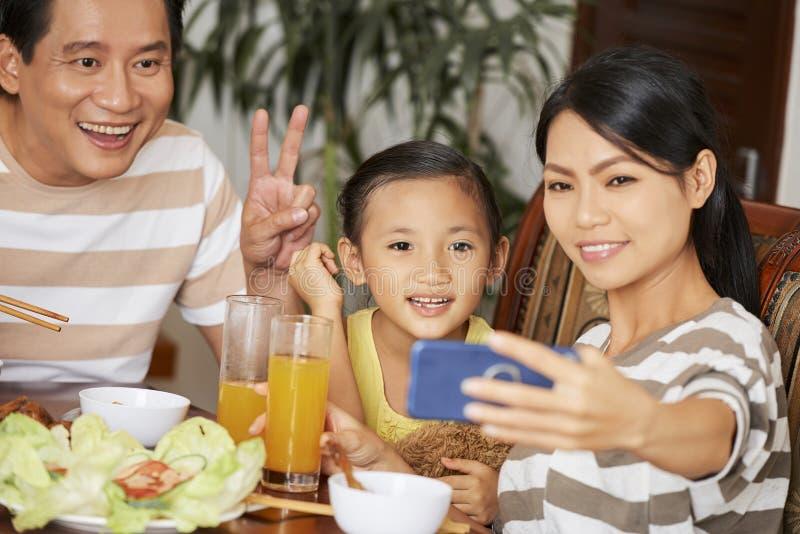 Familjselfiestående under matställe arkivfoto