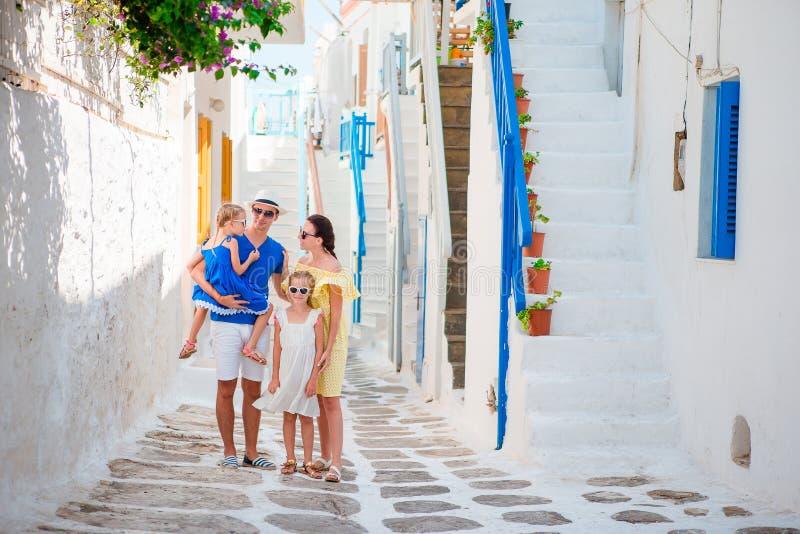 Familjsemester i liten europeisk stad Föräldrar och ungar på gatan av den grekiska traditionella byn på den Mykonos ön arkivfoton