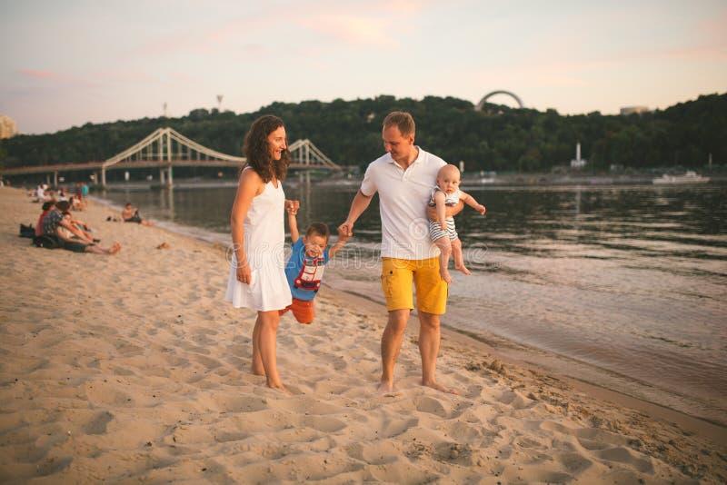 Familjsemester i sommar Ung Caucasian familjfot som g?r den barfota sandiga stranden, kustflodvatten Farsamamma som rymmer h?nder fotografering för bildbyråer