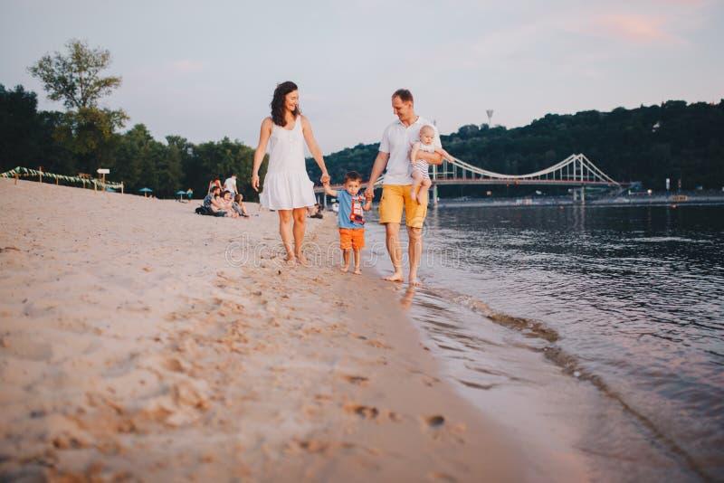 Familjsemester i sommar Ung Caucasian familjfot som g?r den barfota sandiga stranden, kustflodvatten Farsamamma som rymmer h?nder arkivfoto