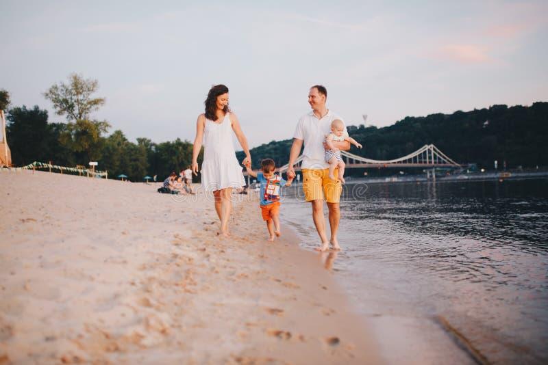 Familjsemester i sommar Ung Caucasian familjfot som g?r den barfota sandiga stranden, kustflodvatten Farsamamma som rymmer h?nder arkivbild