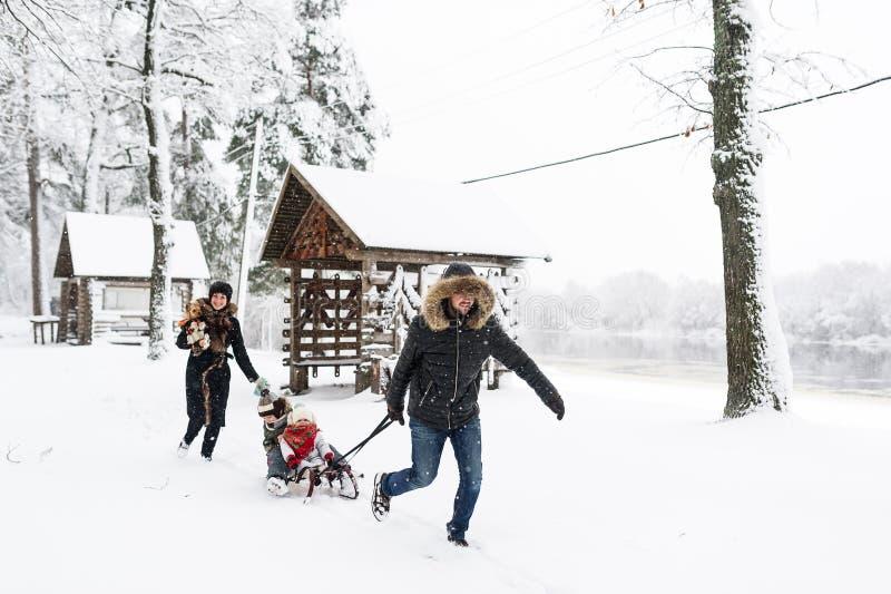 Familjsemester på helg utomhus Små ungar tycker om en släderitt Sledding för barn arkivbild