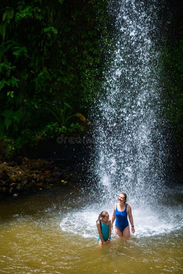 Familjsimning i vattenfall royaltyfri fotografi