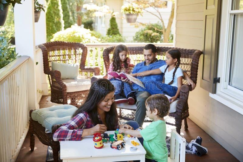 FamiljSit On Porch Of House läseböcker och spelalekar fotografering för bildbyråer